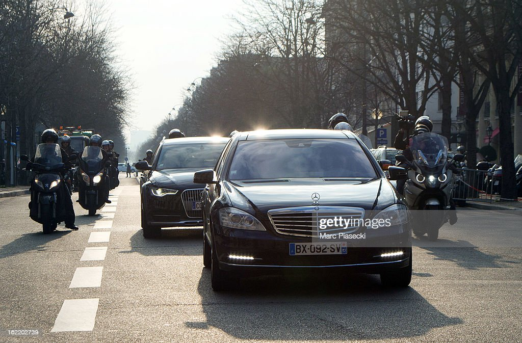 Victoria Beckham's car is surrounded by French media on mopeds as she leaves the 'Yves Saint Laurent' strore on February 20, 2013 in Paris, France.