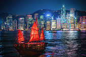 Night view of Victoria Harbour with a junk shop sailing across it.