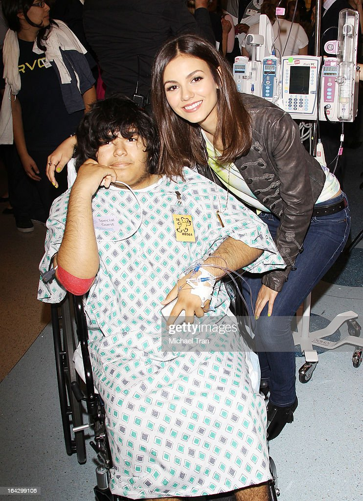 Victoria Justice (R) pose with a young patient from CHOC's Children Hospital at The Ryan Seacrest Foundation West Coast debut of new multi-media broadcast center 'Seacrest Studios' held at CHOC Children's Hospital on March 22, 2013 in Orange, California.