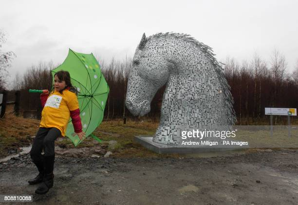 Victoria Primary School pupil Abbie Cockburn struggles in the wind and rain next to a ten foot Kelpie at the site where a pound43 million tourist...