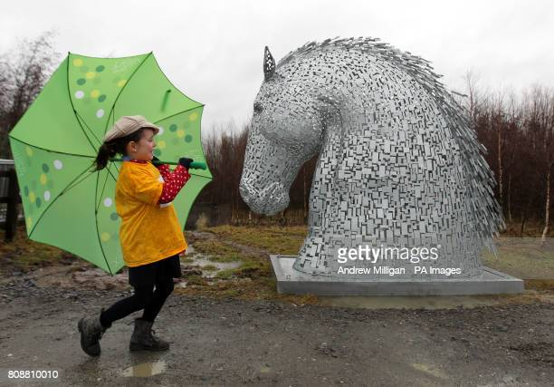 Victoria Primary School pupil Willow Hanley struggles in the wind and rain next to a ten foot Kelpie at the site where a 43 million tourist...