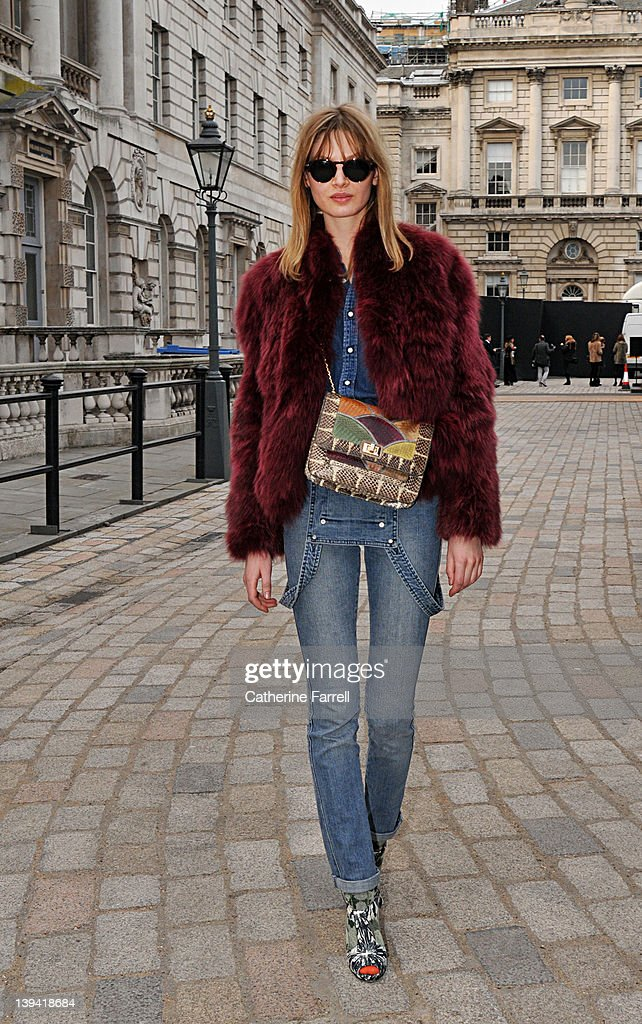 Victoria Sekrier, Stylist and Model wearing Vintage Burgundy fun fur jacket, Levi Denim shirt, Levi Denim dungarees, Angela Jackson bag, Kat Maconie print shoes, Orange socks by Happy, Accessories Angela Jackson bag and Hugo Boss sunglasses at London Fashion Week Autumn/Winter 2012 at on February 20, 2012 in London, England.