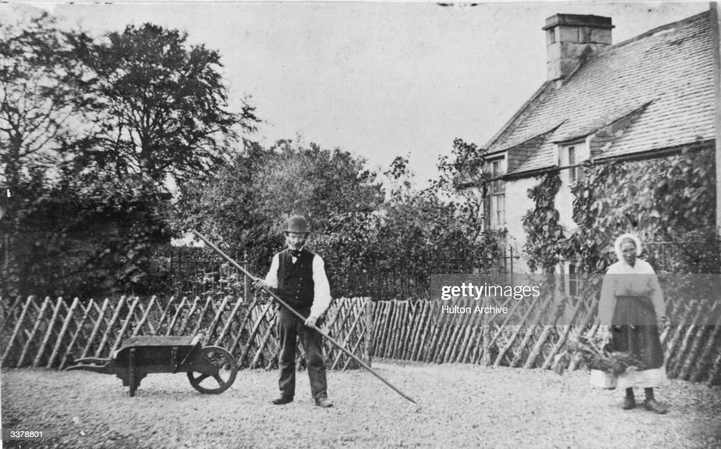 Victorian couple tending to the garden of their cottage
