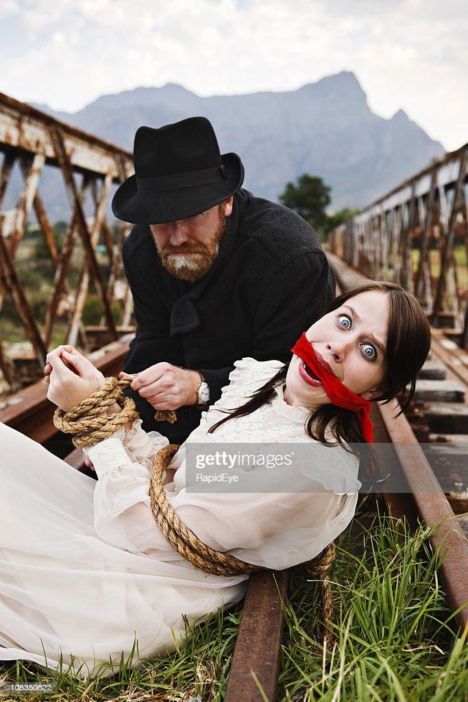 Victorian melodrama as villain ties terrified maiden to railway track : Stock Photo