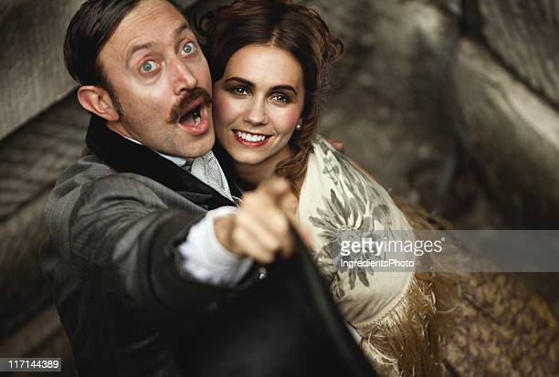 Victorian romantic couple, excited man points in the air.