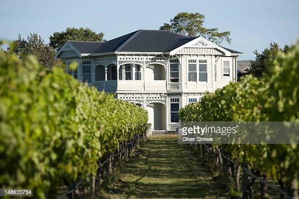 Victorian style wooden house set amongst vineyards.