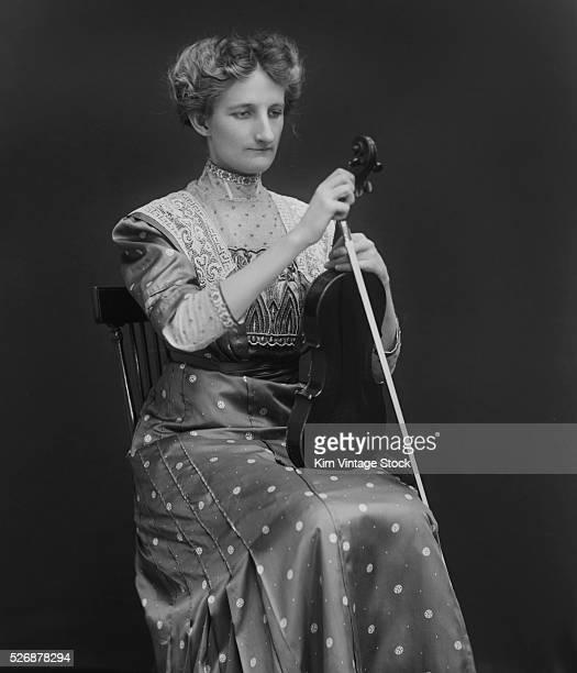 A Victorian woman tunes her violin ca 1898