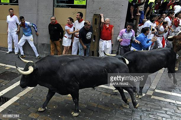 Victoriano del Rio Cortes' bulls run in a street as people stand near a wall during the third bullrun of the San Fermin Festival in Pamplona northern...