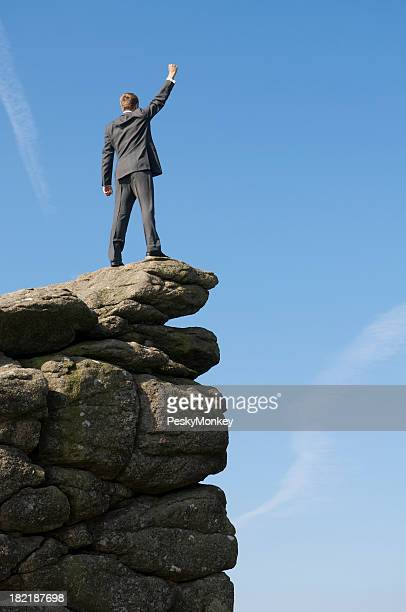 Victorious Businessman Standing Outdoors on Mountaintop