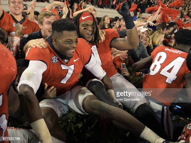 A victorious Georgia Bulldogs linebacker Lorenzo Carter and Georgia Bulldogs linebacker Keyon Brown celebrates with fans after the game between the...