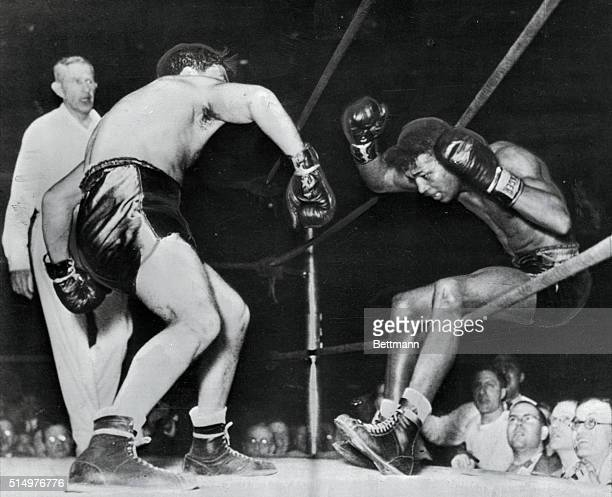 Victorious in 129 successive fights including 40 as a pro Ray Robinson falls through the ropes of a Detroit ring under the impact of Jake LaMotta's...