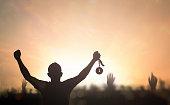 Silhouette winner hand holding gold medal reward against blurred sport stadium sunset background