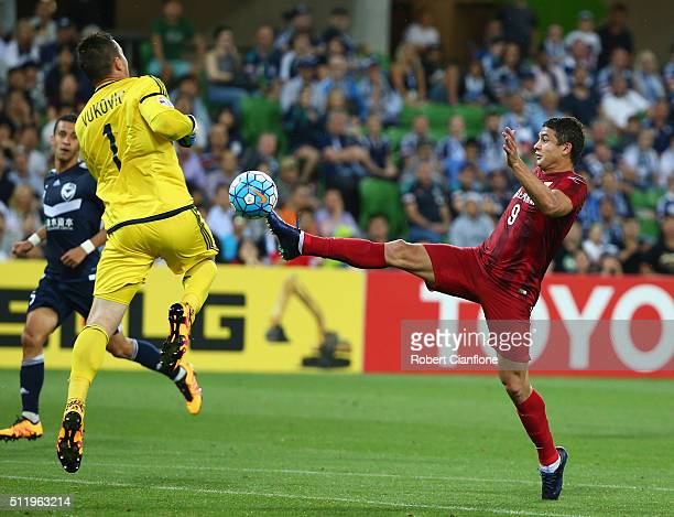 Victory goalkeeper Danny Vukovic is challenged by Elkeson of Shanghai SIPG during the AFC Asian Champions League match between Melbourne Victory and...
