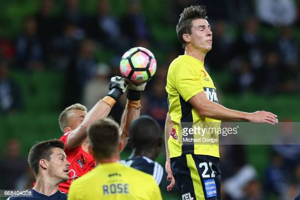 Victory goalkeeper Lawrence Thomas saves a goal attempt by punching the ball away from cof the Mariners during the round 27 ALeague match between the...