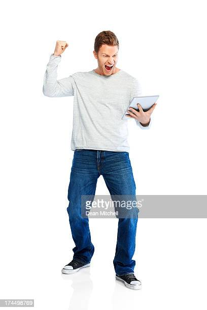 Victory - Successful young man raising fist using tablet pc