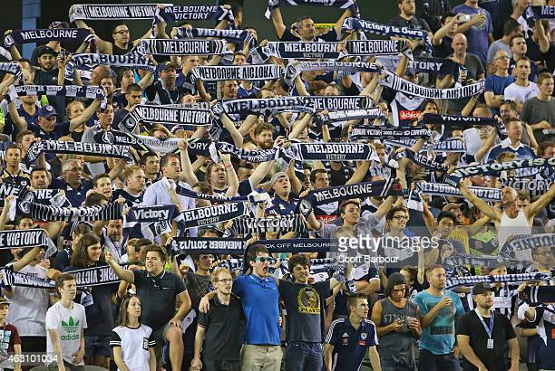 Victory supporters in the crowd hold their scarves aloft as the teams line up before the round 16 ALeague match between Melbourne Victory and...