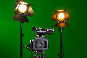 A video camera and a spotlight with a Fresnel lens on a green background. Filming in the interior. The chroma key.