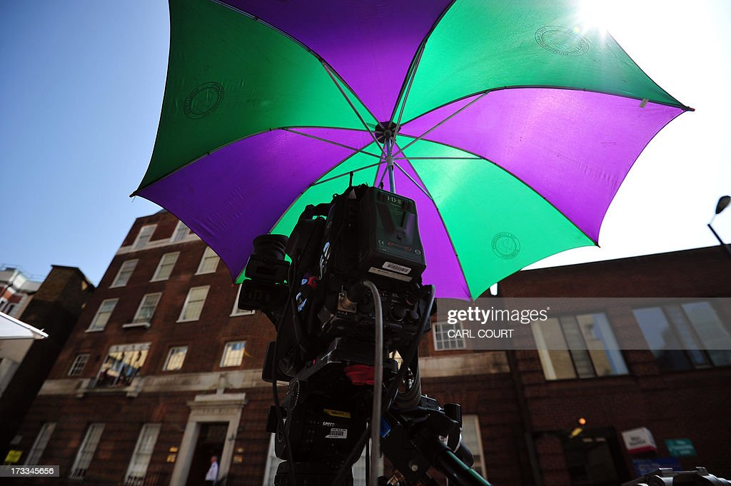 A video camera covered by an umbrella is pictured outside the Lindo Wing of Saint Mary's Hospital in London, on July 12, 2013, where Prince William and his wife Catherine's baby will be born. Britain's royal family and the world's media are on tenterhooks awaiting the birth of Prince William and wife Catherine's first child, a baby who will one day be king or queen of Britain and a diverse group of commonwealth countries.