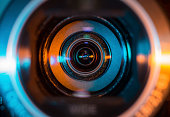 Video camera lens lit in blue and orange