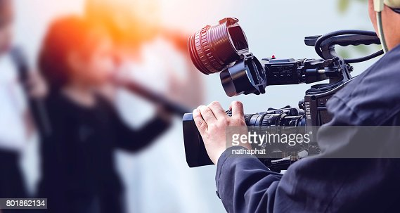 Video camera operator working with his equipment : Stock Photo