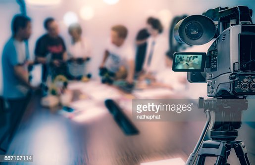 Video camera taking live video streaming at people working background : Foto stock