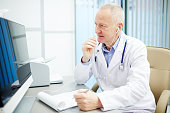 Contemporary doctor in earphones consulting patients through video calling while sitting in front of computer monitor by workplace