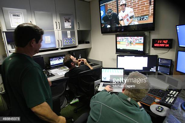 Video Coordinator Adam Rhoden of the Oakland Athletics helps get video ready for Craig Gentry and Third Base Coach Mike Gallego in the clubhouse...