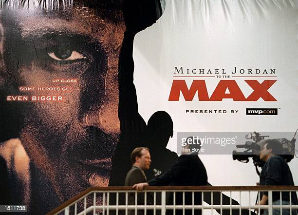 A video crew interviews a guest in front of a promotional billboard May 4 2000 after he attended the world premiere of the new IMAX movie starring...