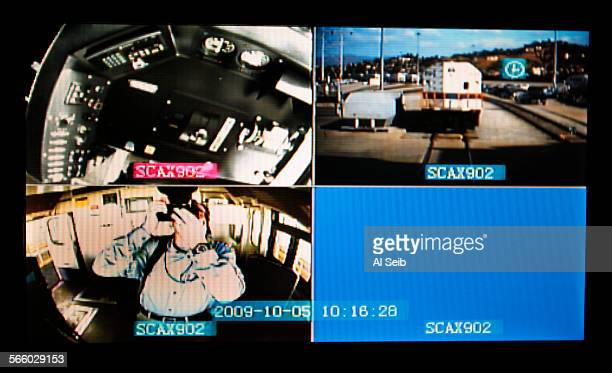 A video display inside the locomotive cabin shows the view of an outward–facing camera and two inward–facing cameras that have been installed in a...