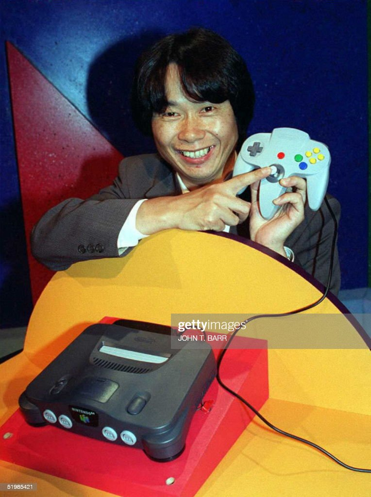 Video game designer, Shigeru Miyamoto from Japan, points to the handset of the new Nintendo 64 flagship game, Super Mario 64, at the Los Angeles Electronic Entertainment Expo 15 May. The world's first true 64-bit video game system will produce three-dimensional environments and is equal to the power of ten Pentium chips bundled together making it the most powerful video game.