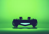 Video game joystick or controller on a vivid green graduated background with copy space viewed low angle in an eye-catching design template