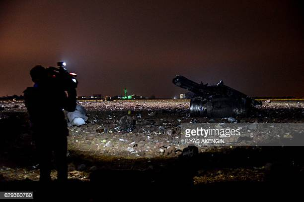 A video journalist captures footage beside the wreckage of a Turkish F16 war plane which crashed in Diyarbakir on December 12 2016 A Turkish fighter...