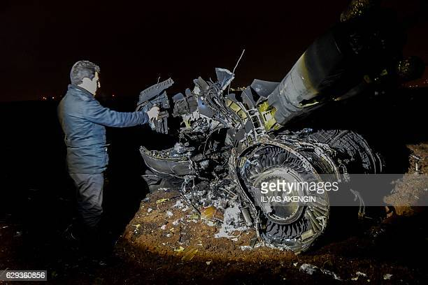 TOPSHOT A video journalist captures footage beside the wreckage of a Turkish F16 war plane which crashed in Diyarbakir on December 12 2016 A Turkish...