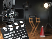 Video, movie, cinema concept. Retro camera, flash, clapperboard and director's chair in dark studio with dof effect. 3d