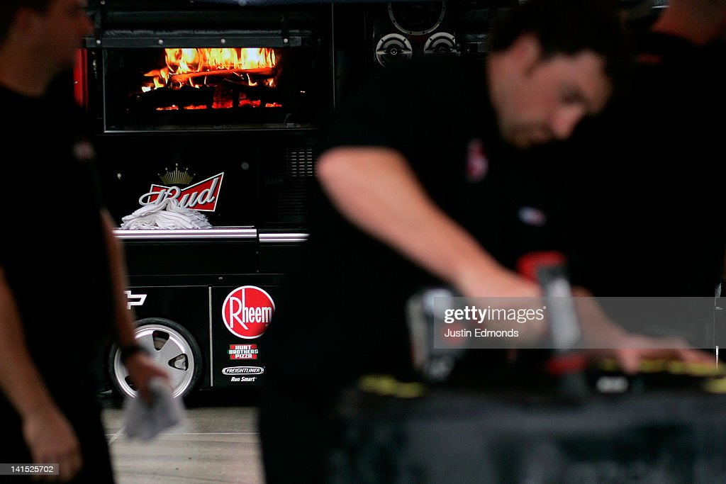 A video screen displays a fire in the background as crew members of the#29 Budweiser Chevrolet driven by Kevin Harvick prepare tires for the race prior to the NASCAR Sprint Cup Series Food City 500 at Bristol Motor Speedway on March 18, 2012 in Bristol, Tennessee.