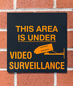 This area under video surveillance sign on a brick wall. The sign is black with orange text.
