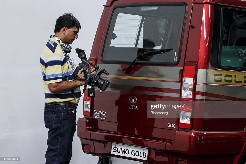 A videographer checks his camera beside a Tata Motors Ltd Sumo Gold GX sport-utility vehicle (SUV) on display during a Tata Motors media event in Pune, India, on Wednesday, June 19, 2013. Tata Motors announced the introduction of 8 new models today. Photographer: Dhiraj Singh/Bloomberg via Getty Images