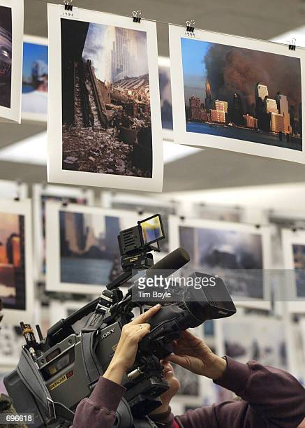 Videographer Jacqueline Denn videotapes photos on display January 31 2002 in Chicago at a press preview for 'here is new york a democracy of...