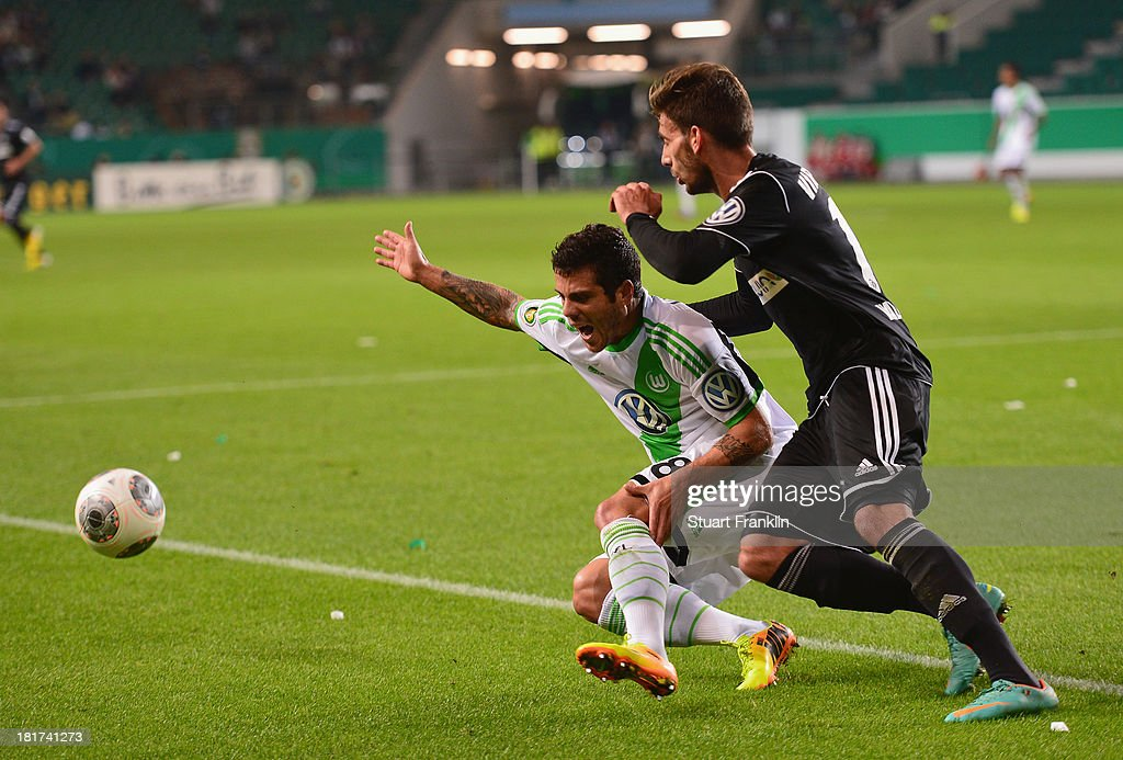 Vieirinha of Wolfsburg is injured in a challenge with Enrico Valentini of Aalen during the second round DFB cup match between VfL Wolfsburg and Vfr Aalen at Volkswagen Arena on September 24, 2013 in Wolfsburg, Germany.