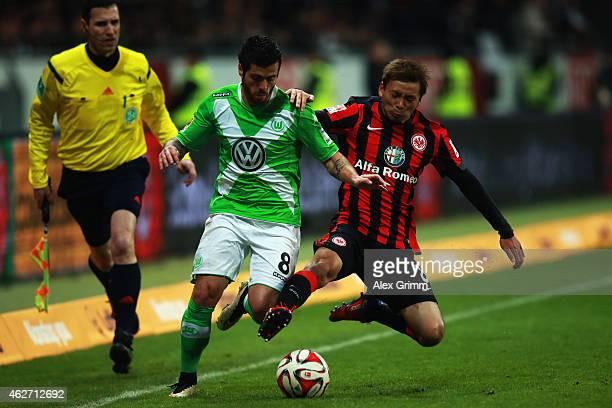 Vierinha of Wolfsburg is challenged by Takashi Inui of Frankfurt during the Bundesliga match between Eintracht Frankfurt and VfL Wolfsburg at...