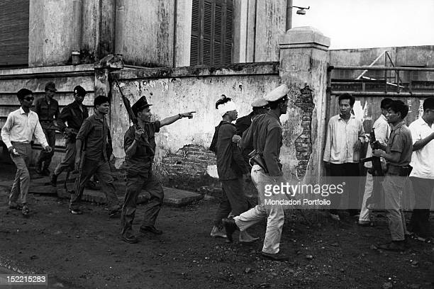 A Viet Cong prisoner wounded in the head is led away by some soldiers before some passerby Saigon 1968