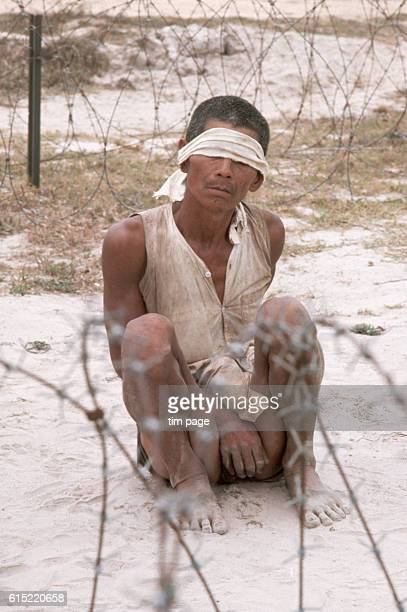 A Viet Cong suspect captured by the US 25th Division north of Parrots Beak squats blindfolded behind a barbed wire enclosure | Location north of...