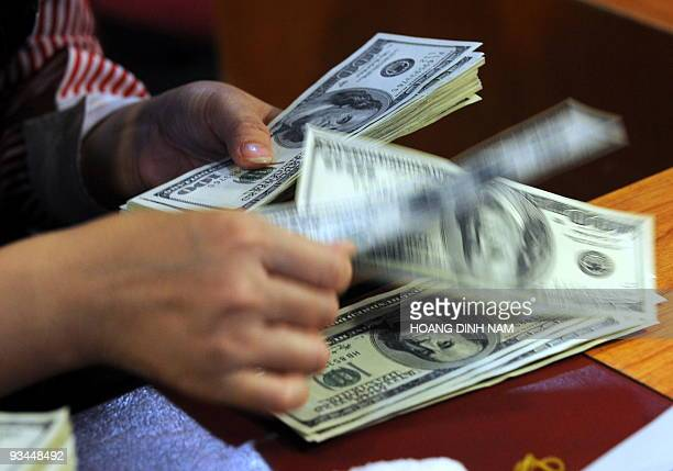 A Vietamese commercial bank employee counts US dollar notes at a branch in Hanoi on November 26 2009 Vietnam's central bank devalued its currency and...