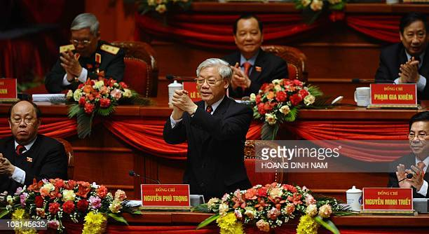 Vietnam Communist Party's newly elected Secretary General Nguyen Phu Trong acknowledges as delegates clap to congratulate him during the closing...