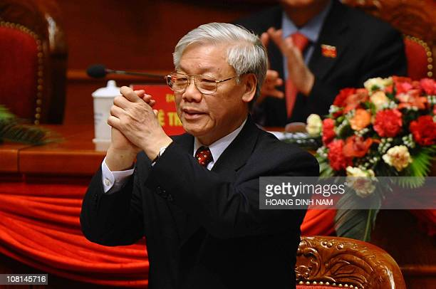 Vietnam Communist Party's newly elected Secretary General Nguyen Phu Trong acknowledges members as he is greeted by delegates during the closing...