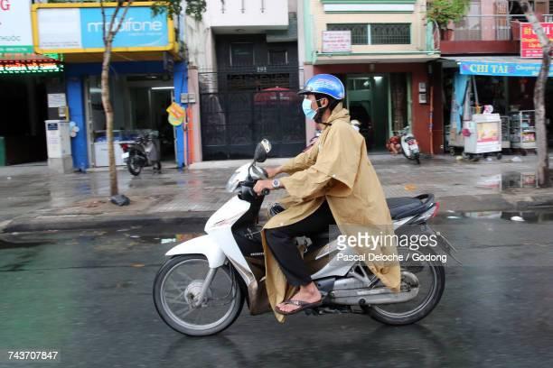 Vietnam, Ho Chi Minh City. Heavy monsoon rain.  Motor Scooters on Saigon Street.  Vietnam.