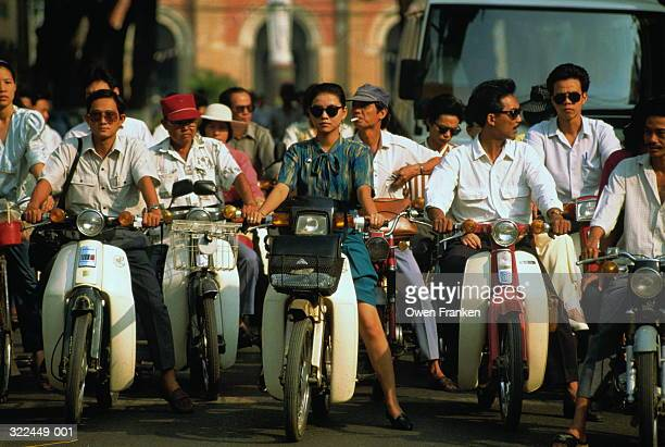 Vietnam, Ho Chi Minh City, people riding mopeds in city street