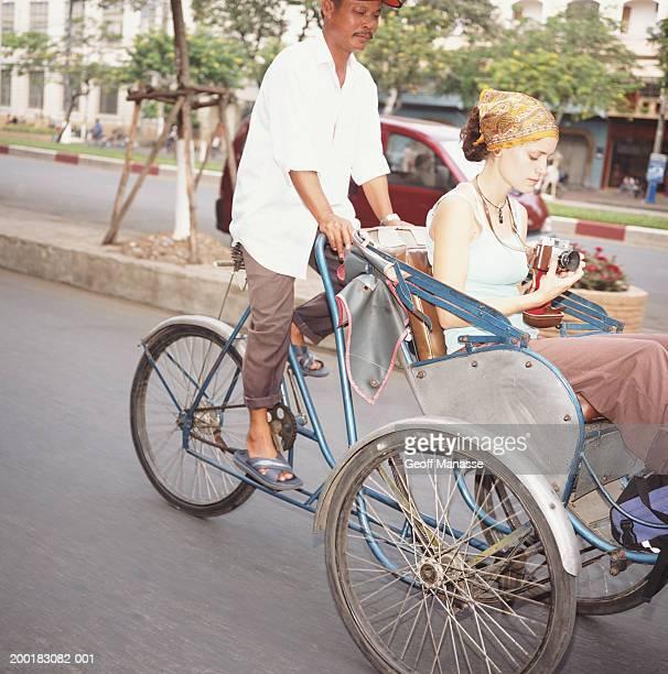 Vietnam, Ho Chi Minh City, young woman riding on pedicab