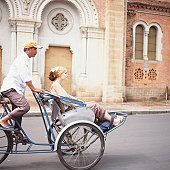 Vietnam, Ho Chi Minh City, young woman riding on pedicab, side view