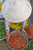 Vietnam, Hoi An, woman bending over vegetables at market